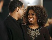 """<p>Producer Oprah Winfrey (R) smiles to cast member and director of the movie Denzel Washington at the premiere of """"The Great Debaters"""" at the Arclight Cinerama Dome in Hollywood, California in this December 11, 2007 file photo. REUTERS/Mario Anzuoni</p>"""
