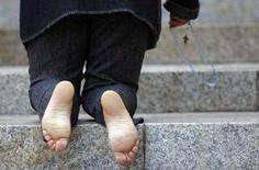<p>Una donna prega in ginocchio sugli scalini del santuario di Padre Pio a San Giovanni Rotondo. REUTERS/Alessandro Bianchi</p>