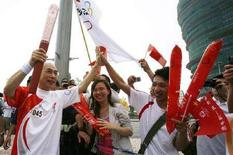 <p>Un tedoforo festeggiato durante la corsa della fiaccola olimpica a Macao, il 3 maggio 2008. REUTERS/Claro Cortes IV</p>