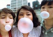 <p>Tre ragazze orientali fanno le bolle con i chewing gum. REUTERS/Jonathan Drake JD/CP</p>