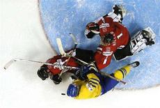 <p>Switzerland's goalie Jonas Hiller (R) hits Sweden's Tony Martensson (bottom) during the third period of action at the 2008 IIHF World Hockey Championships in Quebec City May 7, 2008. REUTERS/Mathieu Belanger</p>