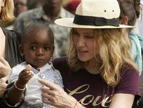 <p>Madonna holds her adopted son, David Banda, at an orphan care centre run by Raising Malawi, a grassroots initiative by Madonna, in Mphendula Village, about 25 miles from the capital Lilongwe April 19, 2007. REUTERS/Siphiwe Sibeko</p>