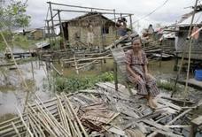 <p>Mulher de Mianmar espera homens construírem um abrigo em vila afetada pelo ciclone Nargis, em 14 de maio de 2008  REUTERS. Photo by Reuters</p>