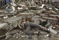 """<p>Тело одной из жертв землетрясения в Китае под обломками разрушенного здания в округе Бэйчуань, провинция Сычуань, 14 мая 2008 года. оличество погибших в результате разрушительного землетрясения в Китае превысило 19.500 человек, сообщило в четверг китайское информагентство """"Синьхуа"""" со ссылкой на власти провинции Сычуань, наиболее пострадавшей в результате подземных толчков. (REUTERS/Guangquan)</p>"""