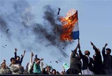 """<p>Afghans burn a Netherlands flag during a protest in Kabul March 21, 2008. Some 5,000 Afghans chanted """"death to Denmark and """"death to the Netherlands"""" in the capital Kabul on Friday, protesting the reprinting of a cartoon of the Prophet Mohammad in Danish newspapers and a Dutch film on the Koran. REUTERS/Ahmad Masood</p>"""