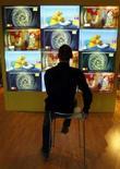<p>Un uomo davanti ad alcuni schermi televisivi a Cannes. REUTERS/Eric Gaillard (FRANCE)</p>