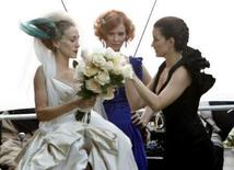 """<p>Actresses Sarah Jessica Parker (L), Cynthia Niixon and Kristin Davis look at a bouquet as they wait to film a scene on the set of """"Sex in the City:The Movie"""" in New York October 12, 2007. REUTERS/Brendan McDermid</p>"""