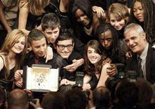 """<p>French director Laurent Cantet (R) poses for photographers surrounded by students holding the Palme d'Or award for their film """"Entre les Murs (The Class)"""" during the award ceremony at the 61st Cannes Film Festival May 25, 2008. REUTERS/Eric Gaillard</p>"""