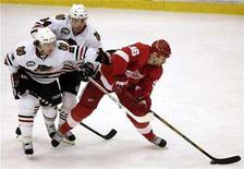 <p>Detroit Red Wings leftwing Tomas Holmstrom (R) keeps the puck from Chicago Blackhawks center Yanic Perreault (C) and defenseman Duncan Keith during the third period of their NHL hockey game in Detroit, Michigan April 6, 2008. REUTERS/Rebecca Cook</p>