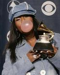 """<p>Missy Elliott blows a bubble while chewing gum as she holds the Grammy award she won for best short form music video for """"Lose Control"""" at the 48th annual Grammy Awards in Los Angeles February 8, 2006. REUTERS/Robert Galbraith</p>"""