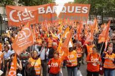 <p>Manifestantes seguram faixas de sindicatos durante protesto em Paris. Dezenas de milhares de trabalhadores franceses fizeram manifestações contra os planos do governo de reformar o sistema de aposentadoria e a semana de trabalho de 35 horas. Photo by Benoit Tessier</p>