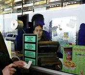 <p>A movie goer picks up tickets February 25, 2004 at a movie theater in Dallas, Texas. REUTERS/Jeff Mitchell</p>