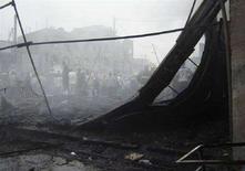<p>Жители собираются на месте взрыва грузовика в Багдаде 17 июня 2008 года. Не менее 11 человек погибли, и еще 38 были ранены в результате взрыва заминированного автомобиля на автобусной остановке в Багдаде, сообщила иракская полиция. (REUTERS/Stringer)</p>