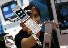 <p>Una mujer posa con el móvil robot de SoftBank Mobile Corp, 'Phone Braver 815T PB', en la feria internacional de juguetes de Tokio, en Tokio, jun 19, 2008. Softbank, el tercer mayor operador de telefonía móvil de Japón, dijo el lunes que distribuirá el nuevo aparato iPhone en el país asiático a un precio de 23.040 yenes (214,6 dólares). Softbank y su principal rival, NTT DoCoMo, han estado disputándose el derecho a lanzar el iPhone en Japón, pero fue el primero el que logró el contrato para vender el esperado dispositivo multimedia a partir del próximo 11 de julio. Photo by (C) TORU HANAI / REUTERS/Reuters</p>