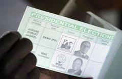 <p>Un funzionario elettorale dello Zimbabwe tiene in mano una scheda elettorale in cui compaiono le immagini e i nomi di Robert Mugabe e del leader dell'opposizione Morgan Tsvangirai. REUTERS/Philimon Bulawayo</p>