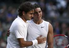 <p>O espanhol Rafael Nadal (dir) é cumprimentado pelo suíço Roger Federer após final em Wmbledon, dia 6 de julho. A imprensa espanhola proclamou Rafael Nadal como o melhor tenista do mundo após a vitória épica na final de Wimbledon contra Roger Federer. Photo by Pool</p>