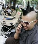 <p>El admirador de Apple Koichi Funyu habla por su teléfono móvil mientras espera en una fila para comprar un nuevo iPhone en Tokio, 9 jul 2008. El nuevo iPhone atraerá una multitud de compradores cuando salga a la venta el viernes en más de 20 países, lo que ayudará a Apple Inc a alcanzar fácilmente la meta de ventas de 10 millones de unidades hacia finales del 2008. El ampliamente anticipado teléfono inteligente tiene navegación en internet más rápida que el primer iPhone, respaldo para software externo como juegos, y está siendo fuertemente subsidiado por muchos operadores de telefonía, y algunos incluso lo regalan para atraer nuevos suscriptores. Photo by Toru Hanai/Reuters</p>