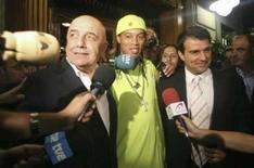 <p>O chefe-executivo do Milan, Adriano Galliani, Ronaldinho e o presidente do Barcelona, Joan Laporta, deixam um restaurante em Barcelona depois de acertarem os termos do contrato de transferência do jogador. Photo by Stringer</p>