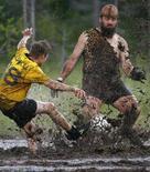 <p>Una partita di calcio nel fango REUTERS/Bob Strong</p>