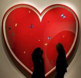 <p>Due fidanzati davanti ad un'opera d'arte a forma di cuore. REUTERS/Alessia Pierdomenico</p>