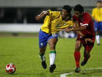 <p>O atacante brasileiro Ronaldinho (esq) protege a bola contra Juma'at Jantan, da seleção de Cingapura, durante amistoso em Cingapura, dia 28 de julho. No primeiro teste para os Jogos Olímpicos, a seleção mostrou dificuldade em jogar pelas laterais, congestionou o meio-campo e teve Ronaldinho Gaúcho durante os 90 minutos para vencer a fraca equipe de Cingapura. Photo by Pablo Sanchez</p>
