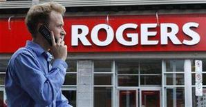 <p>A pedestrian uses his mobile phone while walking past a Rogers store in Ottawa July 21, 2008. REUTERS/Chris Wattie</p>