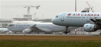 <p>A Cathay Pacific Boeing 747 (L) sits at the airport as an Air Canada jet lands in Vancouver, British Columbia July 29, 2008. REUTERS/Andy Clark</p>