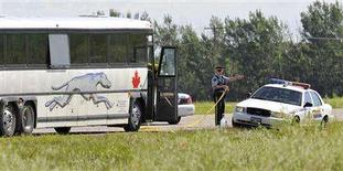 <p>Police investigate the scene around a Greyhound bus about 20 km (12 miles) west of Portage la Prairie, July 31, 2008. A man sleeping on a Greyhound bus as it rolled across the Canadian Prairies was killed and decapitated by his seatmate on Wednesday night, other passengers on the bus told the media. REUTERS/Fred Greenslade</p>