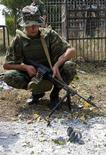 <p>A Georgian soldier looks at a projectile that hit the ground near a cemetery in the village of Upper Nikozi in the Georgian-controlled part of South Ossetia some 100 km (62 miles) from Tbilisi August 2, 2008. REUTERS/Nodar Skhvirashvili</p>
