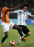 <p>Лайонель Месси из сборной Аргентины (справа) борется за мяч с футболистом Кот-д'Ивуара Секу Сиссе в матче олимпийского турнира в Шанхае 7 августа 2008 года. (REUTERS/Aly Song)</p>