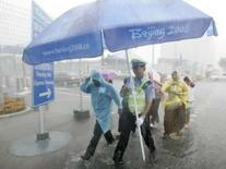 <p>Policial carrega um guarda-chuvas em frente ao ginásio de esgrima, durante temporal em Pequim. Photo by Mikhail Voskresenskiy</p>
