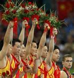 <p>China soma 13 ouros; EUA têm 7. Membros da equipe chinesa de ginástica artística comemoram a conquista da medalha de ouro no pódio. 12 de agosto. Photo by Mike Blake</p>