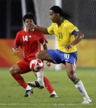 <p>Wan Houliang, da China, tenta roubar a bola de Ronaldinho, na partida ganha pelo Brasil nas olimpíadas de Pequim      REUTERS. Photo by Daniel Aguilar</p>