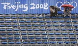 <p>Torcedores se protegem da chuva durante partida de softebol entre EUA e Canadá, nesta quinta-feira, nos Jogos de Pequim. Photo by Danny Moloshok</p>