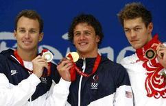 <p>Американские пловцы Аарон Пирсон, Райан Лохт и россиянин Аркадий Вятчанин (слева направо) позируют на пьедестале 15 августа 2008 года. Вятчанин занял третье место на дистанции 200 метров на спине с результатом 1 минута 54,93 секунды. REUTERS/David Gray (CHINA)</p>