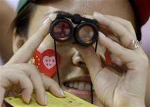 <p>A spectator uses binoculars to watch the Group B men's basketball match between Germany and Angola at the Beijing 2008 Olympic Games August 10, 2008. REUTERS/Sergio Perez</p>