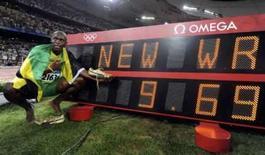 <p>Usain Bolt, da Jamaica, ao lada do placar que registra seu recorde mundial na prova dos 100 metros. Velocista agora corre a prova dos 200 metros e garante que quer o ouro, sem se importar com o recorde. Photo by Kai Pfaffenbach</p>