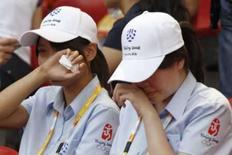 <p>Seguranças do Estádio Olímpico choram devido à desistência do ídolo chinês Liu Xiang da prova dos 110 metros com barreiras, onde era um dos favoritos ao ouro. Photo by Gary Hershorn</p>