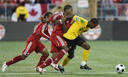 <p>Jamaica's Wolry Wofe battles for the ball with Canada's Patrice Bernier (C) and Julian de Guzman (L) during the first half of their 2010 FIFA World Cup Qualifiers match in Toronto, August 20, 2008. REUTERS/Mark Blinch</p>