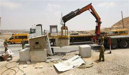 <p>A crane removes concrete blocks at a checkpoint leading to the the West Bank town of Bir Nabala near Ramallah August 21, 2008. REUTERS/Ammar Awad</p>
