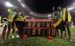 <p>Equipe jamaicana do revezamento 4x100m Asafa Powell, Usain Bolt, Michael Frater e Nesta Carter exibe o recorde mundial estabelecido por eles na final dos Jogos de Pequim, nesta sexta-feira, no estádio Ninho de Pássaro. Photo by Kai Pfaffenbach</p>