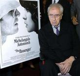 """<p>Legendary Italian film director Michelangelo Antonioni poses alongside a poster for his film """"The Passenger"""" in Beverly Hills in this undated file photo. REUTERS/Chris Pizzello/Files</p>"""