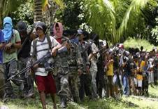 <p>membros do grupo cristão filipino Ilaga marcham ao sul da Filipinas, dia 27 de agosto. As mortes de civis estão aumentando no sul das Filipinas, onde as lutas entre o Exército e as guerrilhas muçulmanas mataram pelo menos 187 pessoas nos últimos 10 dias, informaram o Exército e uma autoridade de direitos humanos na quarta-feira. Photo by Stringer</p>