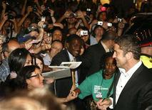 """<p>Actor Gerard Butler (R) signs autographs at the special presentation screening of the film """"RocknRolla"""" at the 33rd Toronto International Film Festival, September 4, 2008. REUTERS/ Mike Cassese</p>"""