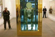 """<p>A visitor looks at """"The Golden Calf"""" by artist Damien Hirst at Sotheby's in London in this September 8, 2008 file photograph. Hirst's bull in a tank of formaldehyde with its head crowned by a gold disc sold for 10.35 million pounds ($18.6 million) on September 15, 2008, a record a auction for one of the contemporary art world's stars, Sotheby's said. REUTERS/Suzanne Plunkett/Files</p>"""