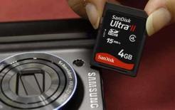 <p>Um consumidor posa com seu cartão de memória SanDisk ao lado de uma câmera Samsung em Hong Kong, no dia 17 de setembro. A fabricante norte-americana de memória flash SanDisk rejeitou uma oferta de aquisição de 5,9 bilhões de dólares apresentada pela fabricante de chips de memória Samsung Electronics, mas não descartou a hipótese de uma transação caso o preço melhore. Photo by Bobby Yip</p>