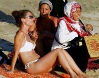 <p>Жительница Индонезии фотографируется с туристкой, загорающей на одном из пляжей острова Бали 29 июля 2006 года. Около 1000 жителей острова Бали вышли на улицы в знак протеста против закона о порнографии, который, как считают его противники, может затронуть местные культурные традиции. REUTERS/Murdani Usman</p>