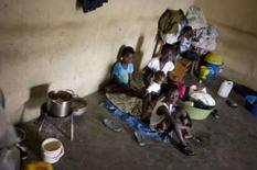 <p>AHaitiana espera, com seus quatro filhos, por comida e atendimento médico em um abrigo na cidade de Hinche. Foto tirada em 18 de setembro de 2008. O haiti foi atingido por duas tempestades tropicais e dois furacões em apenas um mês. Centenas de pessoas morreram. A ONU pede ajuda urgente para o Haiti, que é o país mais pobre do continente americano e não tem condições de bancar os serviços de limpeza e reconstrução. Photo by Eduardo Munoz</p>