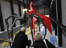 "<p>Visitors to Tate Modern look at an installation by Dominique Gonzalez-Foerster entitled ""TH.2058"" in London October 13, 2008. French artist Gonzalez-Foerster has included two hundred bed frames and a giant spider sculpture based on a work by Louise Bourgeois in her giant installation entitled ""TH.2058"" which fills the cavernous Turbine Hall at London's Tate Modern museum. REUTERS/Suzanne Plunkett</p>"