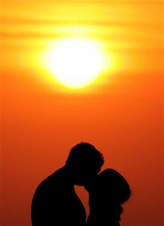 Western tourists kiss during sunset near Kuta beach on the Indonesian resort island of Bali, May 28, 2005. Sex education classes will become compulsory for primary and secondary school children in England to help reduce Britain's high rate of teenage pregnancies, the government is expected to announce on Thursday. REUTERS/Darren Whiteside